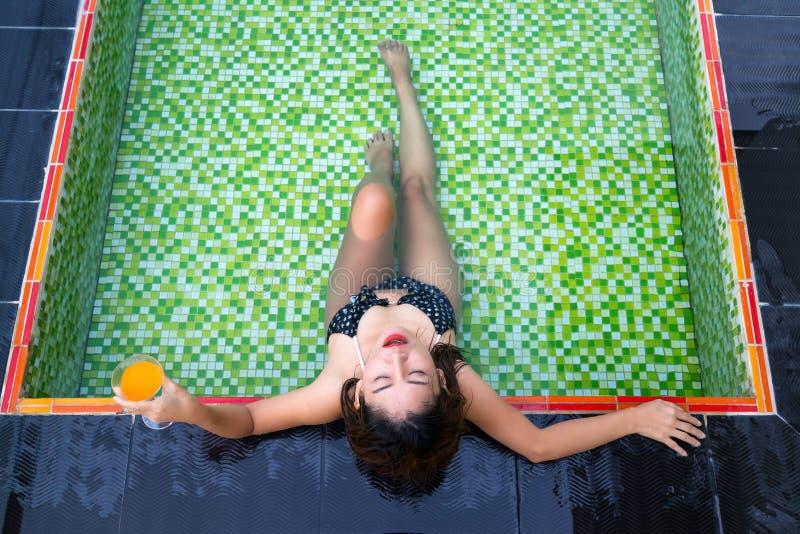 Menina asiática que guarda o vidro do suco de laranja em suas mãos que encontram-se na piscina imagem de stock