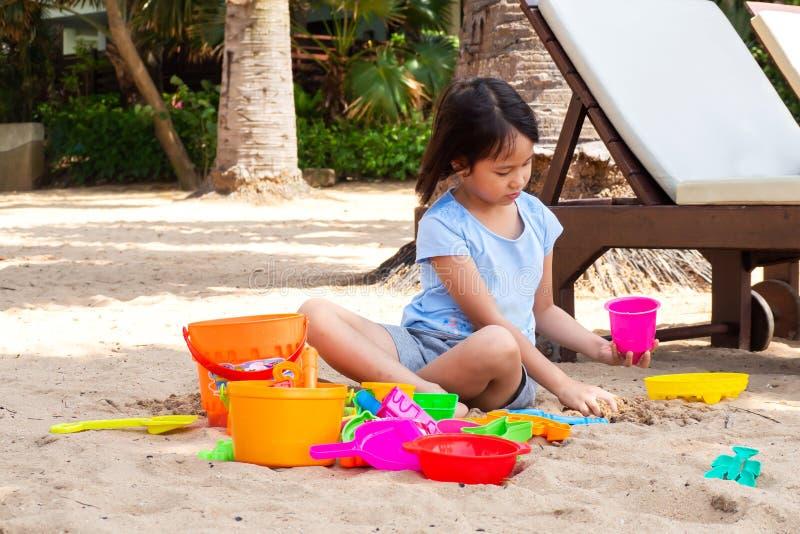 Menina asiática que joga a areia com os brinquedos da areia na praia imagem de stock royalty free