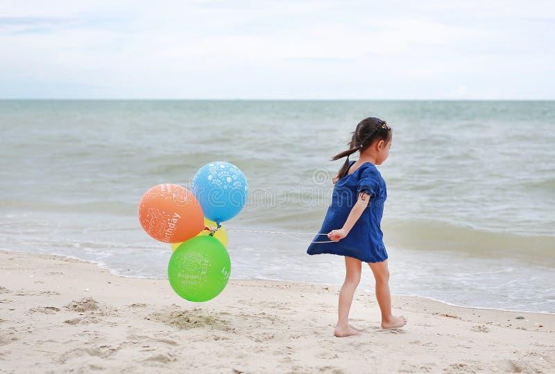 Menina asiática que joga balões na praia fotos de stock