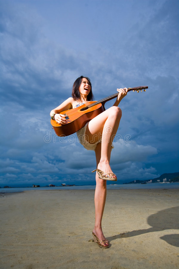 Menina asiática que joga a guitarra na praia foto de stock royalty free