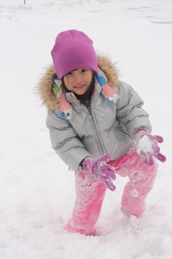 Menina asiática que joga na neve imagem de stock