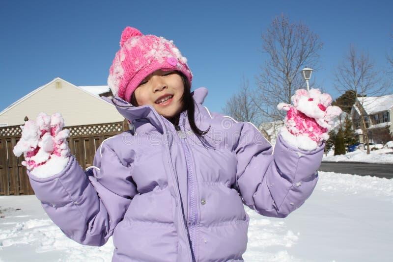 Menina asiática que joga na neve com luvas acima imagens de stock