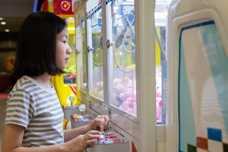 A menina asiática que joga o jogo ou o armário da garra trava a boneca em uma das tomadas do shopping, atividades do feriado de b foto de stock royalty free