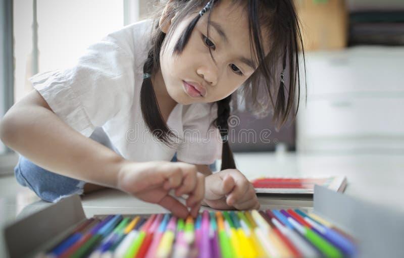 Menina asiática que joga o lápis da cor na sala de visitas home fotos de stock royalty free
