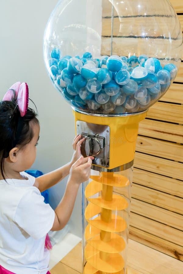 Menina asiática que joga seleccionar afortunado da máquina de venda automática da bola foto de stock