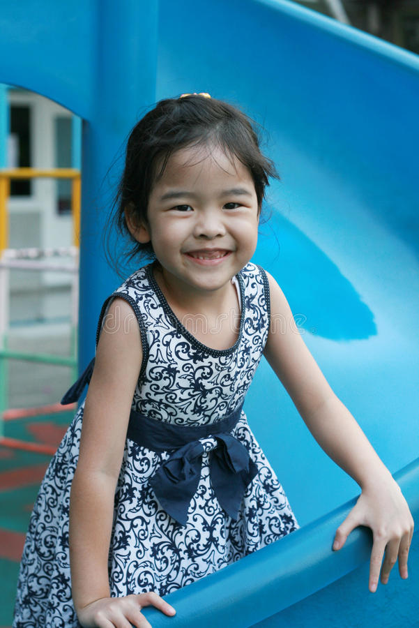 Menina asiática que joga uma corrediça no campo de jogos imagem de stock royalty free