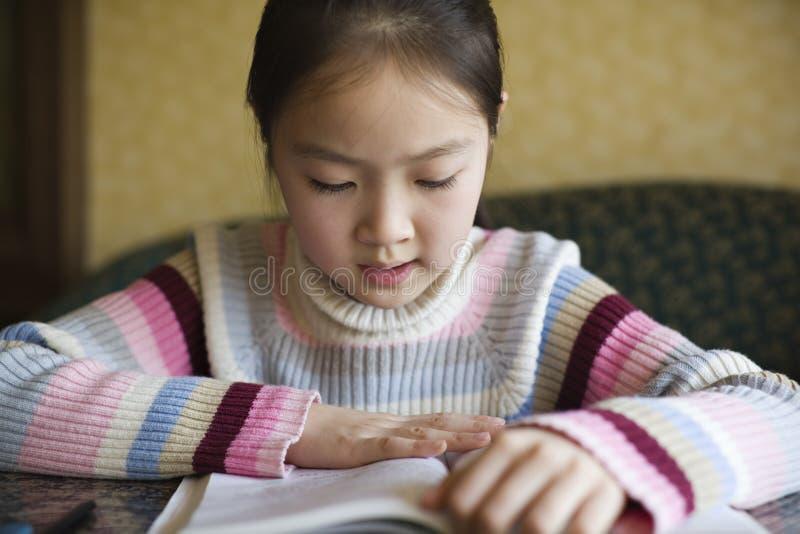 Menina asiática que lê um livro foto de stock royalty free
