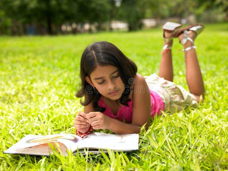 Menina asiática que lê um livro no parque imagens de stock royalty free