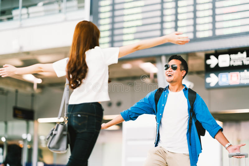 A menina asiática que pegara seu noivo na porta da chegada do ` s do aeroporto, boas vindas para trás dirige do estudo ou do trab fotografia de stock royalty free