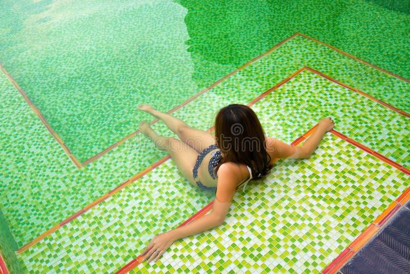 Menina asiática que senta-se na piscina privada imagem de stock royalty free