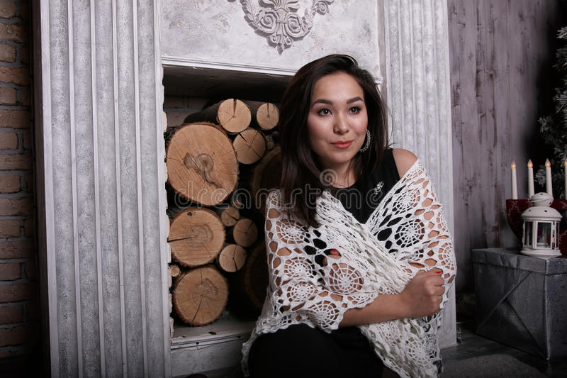 Menina asiática que senta-se perto da chaminé com o xaile em seus ombros foto de stock