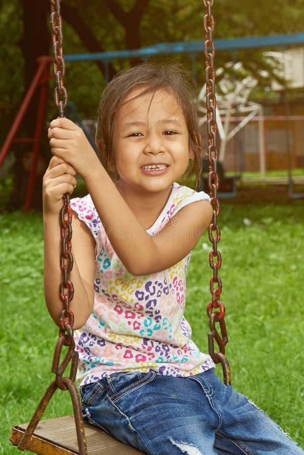 Menina asiática que sorri em um balanço foto de stock