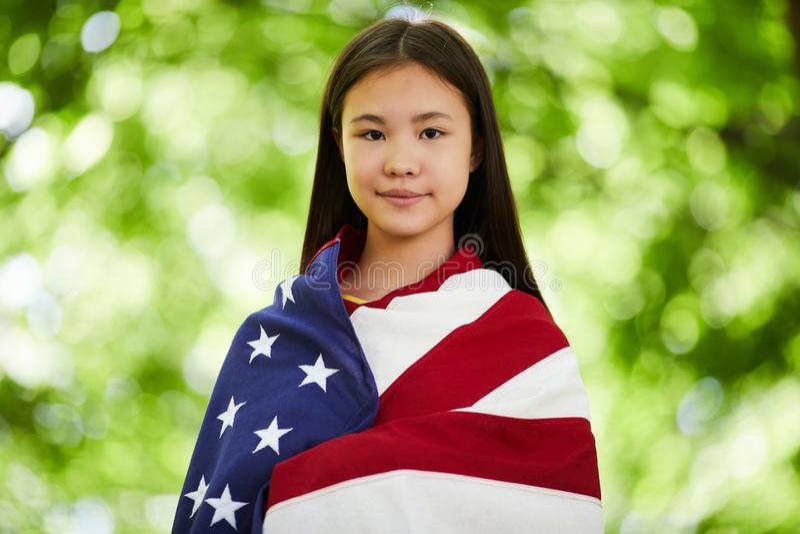 Menina asiática satisfeita coberta com a bandeira americana foto de stock