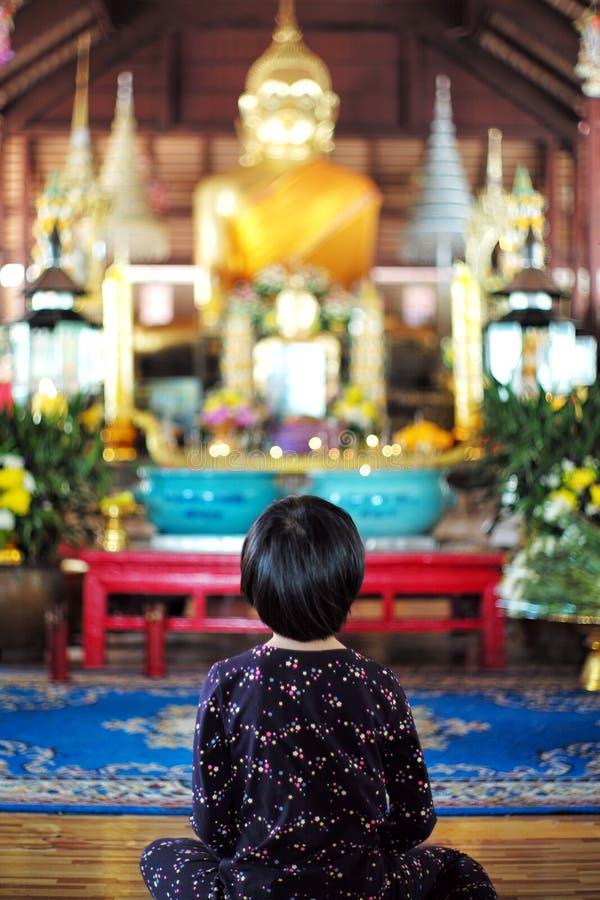 A menina asiática senta-se na frente das estátuas douradas grandes de buddha imagens de stock royalty free