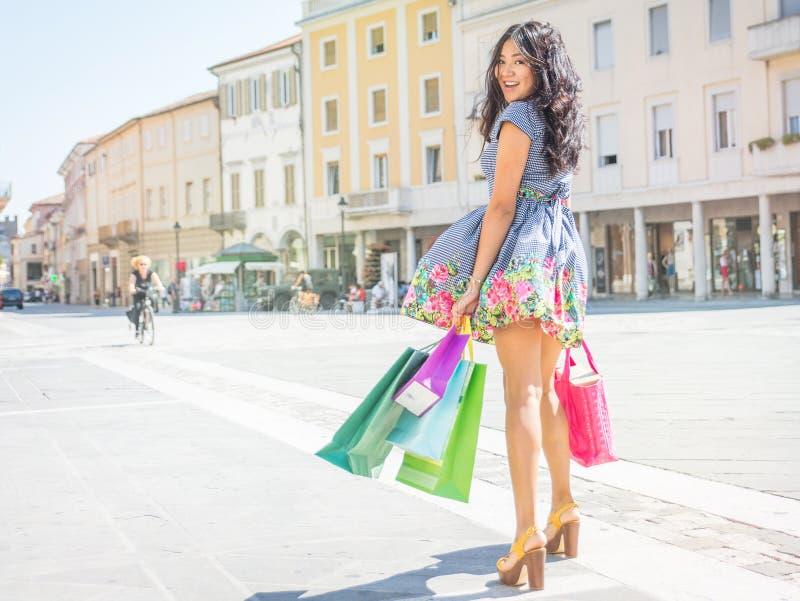 Menina asiática 'sexy' com sacos de compras que anda no centro da cidade imagens de stock