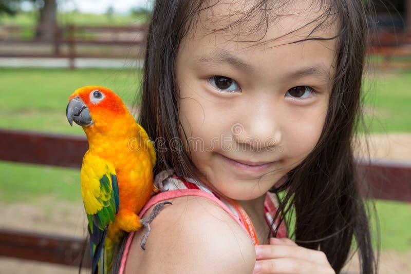 A menina asiática tem um papagaio empoleirado em seu ombro, criança feliz com o pássaro no jardim zoológico foto de stock royalty free