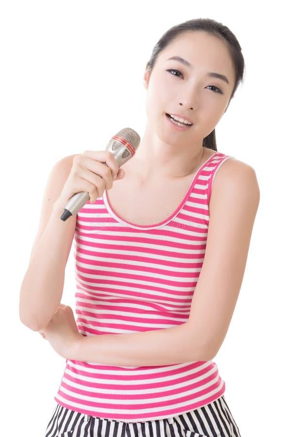 A menina asiática toma um microfone que canta ou fala imagens de stock royalty free