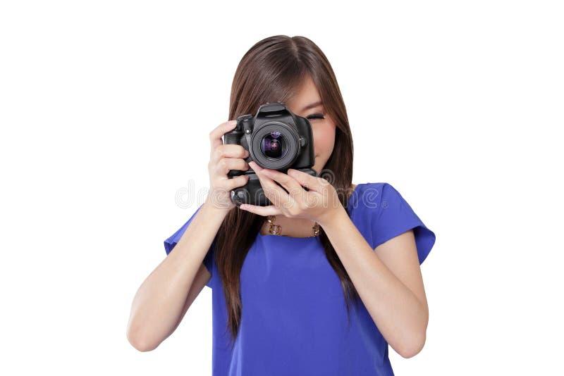 A menina asiática toma uma imagem com câmara digital fotos de stock royalty free