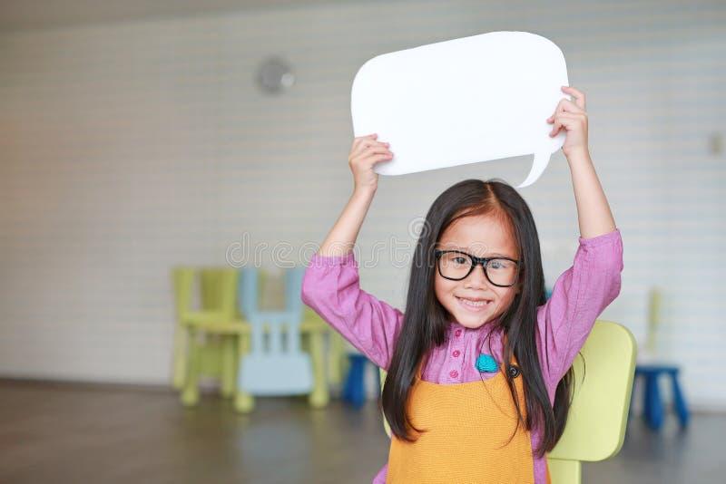 Menina asi?tica ador?vel que guarda a bolha vazia vazia do discurso para dizer algo na sala de aula com sorriso e vista em linha  imagens de stock royalty free