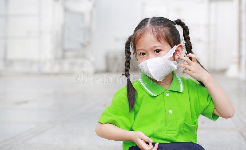 Menina asi?tica da crian?a que veste uma m?scara da prote??o quando fora contra a PM 2 polui??o do ar 5 com apontar acima na cida foto de stock