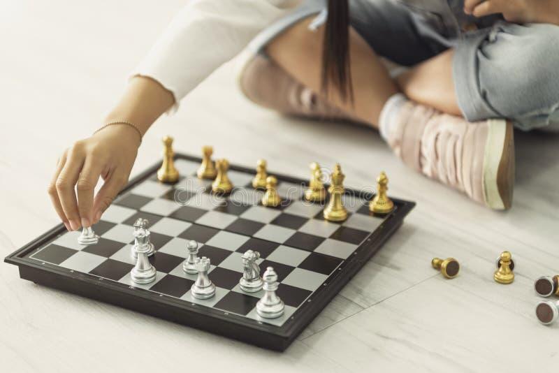 Menina asi?tica feliz que joga a xadrez em casa fotos de stock