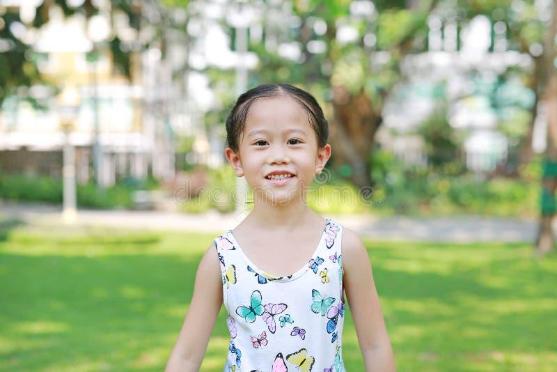 Menina asi?tica pequena de sorriso da crian?a no parque verde ensolarado imagens de stock royalty free