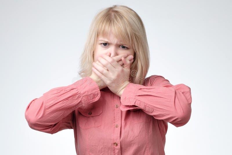 A menina assustado e fecha a boca com suas mãos imagens de stock