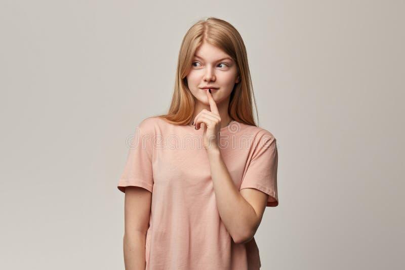 Menina astuto de sorriso atrativa com um dedo em sua boca que comp?e a ideia imagens de stock
