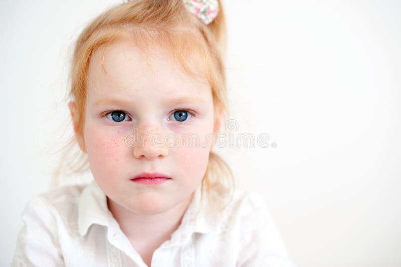 A menina atentamente e olha seriamente para a frente fotografia de stock royalty free