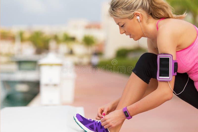 Menina ativa que amarra instrutores antes de exercício running fora foto de stock