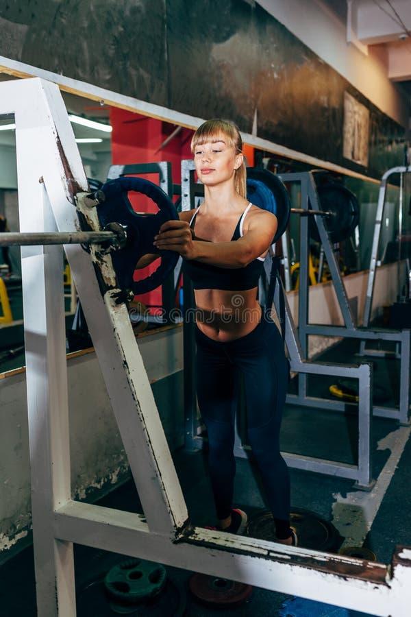 A menina atlética ajusta o peso no barbell no gym fotos de stock