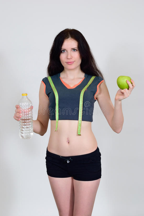 Menina atlética com fita, água e a maçã de medição imagem de stock