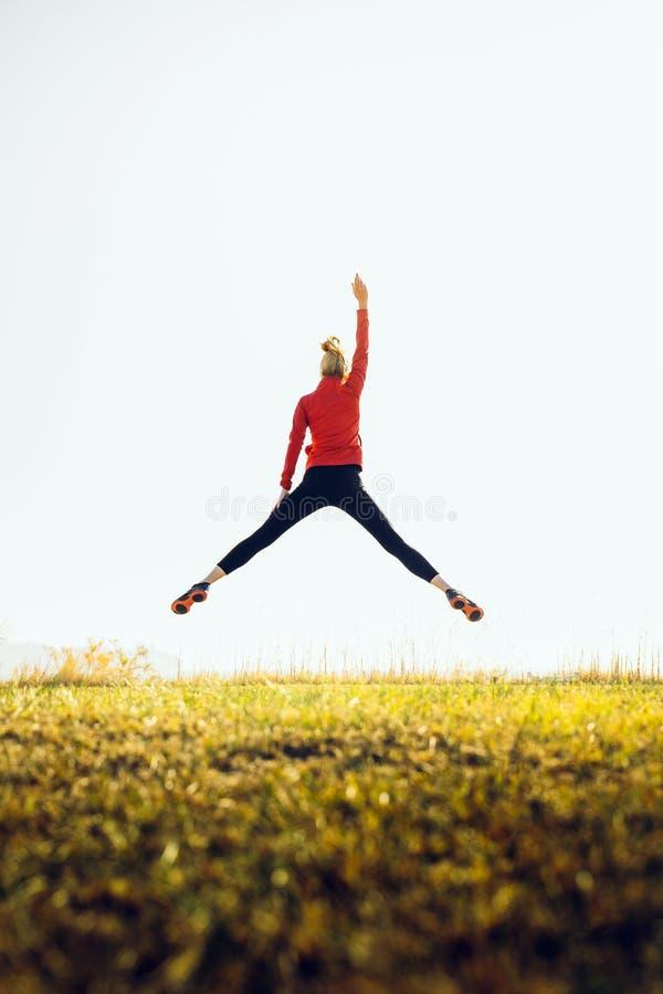 Menina atlética em um salto com a mão levantada O conceito de esporte, estilo de vida saudável e sucesso imagens de stock
