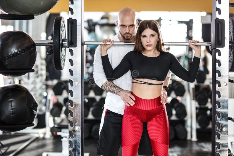 A menina atlética na roupa brilhante à moda dos esportes que faz para trás ocupas e o homem atlético forte ajuda-a no gym moderno imagens de stock royalty free