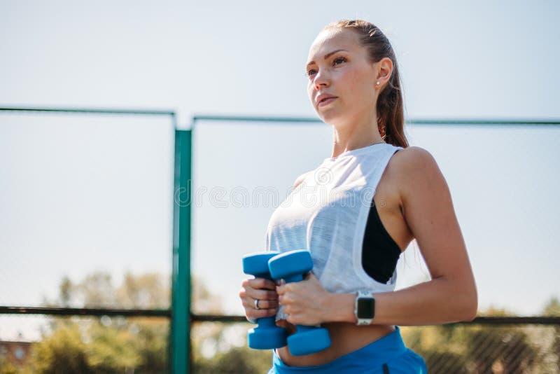 Menina atlética nova que faz exercícios com pesos Levantamento no campo de esportes Retrato Menina da aptidão fotos de stock royalty free