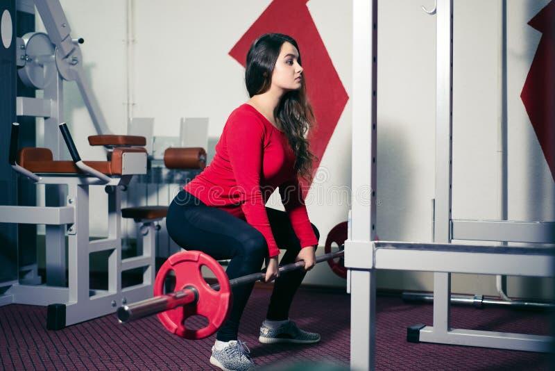 Menina atlética que guarda um barbell em suas mãos a mulher bonita faz a ocupa dos exercícios físicos com parte traseira reta no  foto de stock royalty free