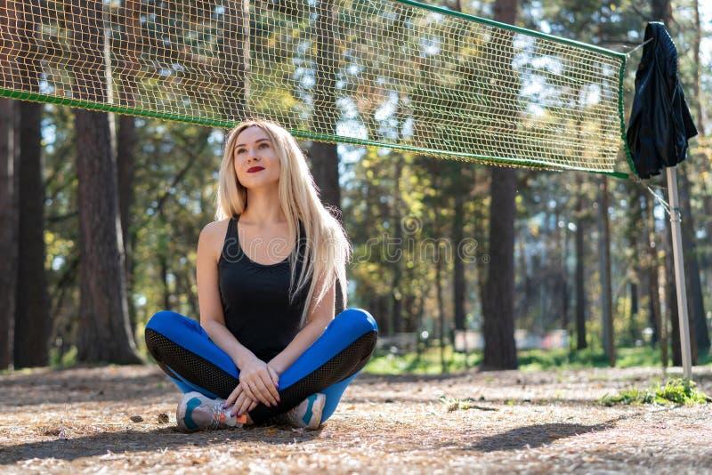 Menina atlética que senta-se em um campo de tênis foto de stock royalty free