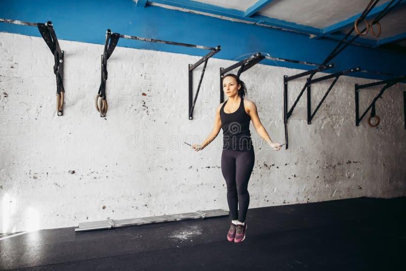 Menina atlética que usa cordas de salto para ela exercício em um gym foto de stock royalty free