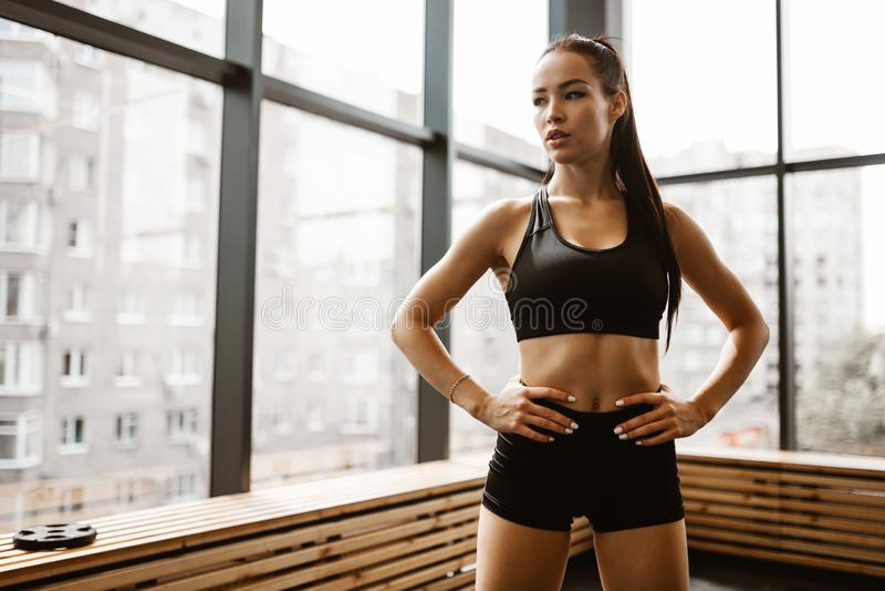 Menina atl?tica bonita com o cabelo marrom vestido na parte superior dos esportes e em suportes pretos do short no gym fotos de stock