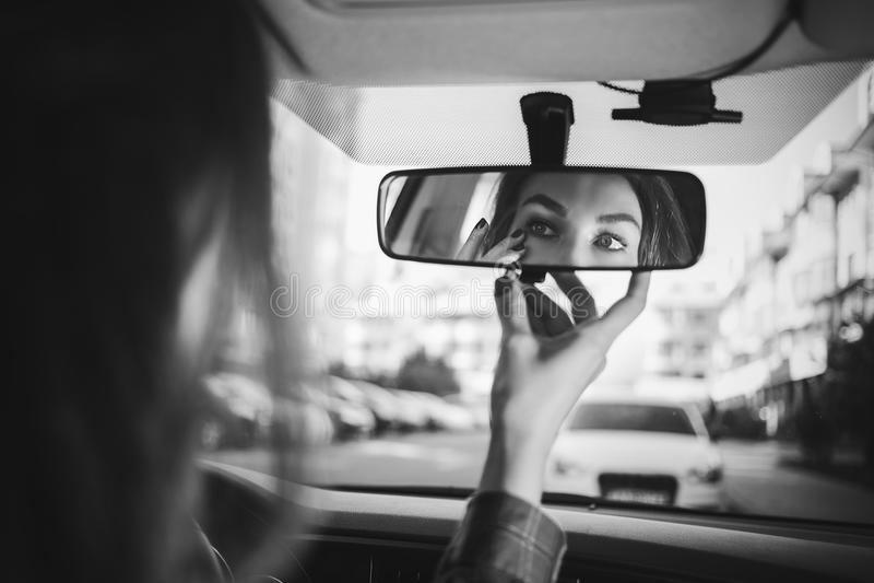 A menina atrás da roda olha no espelho retrovisor no carro e faz-se uma composição em preto e branco imagens de stock