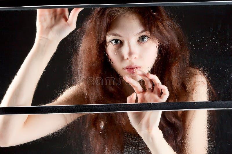 Menina atrás do vidro molhado na obscuridade fotografia de stock