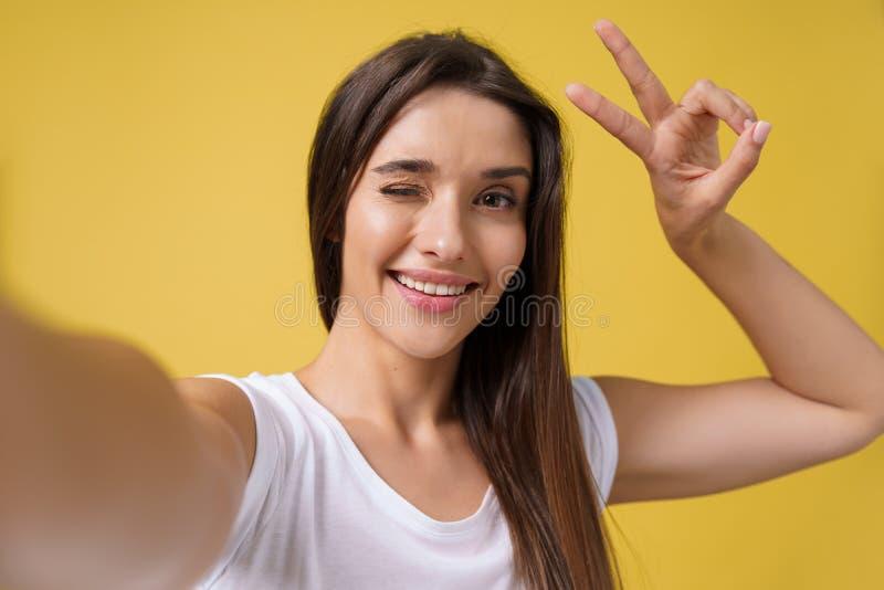 Menina atrativa agradável que faz o selfie no estúdio e no riso Jovem mulher bonita com o cabelo marrom que toma a imagem imagem de stock