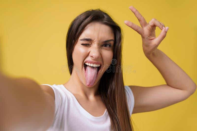Menina atrativa agradável que faz o selfie no estúdio e no riso Jovem mulher bonita com o cabelo marrom que toma a imagem fotos de stock