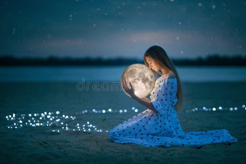 A menina atrativa bonita em uma praia da noite com areia e estrelas abraça a lua, fotografia artística imagem de stock