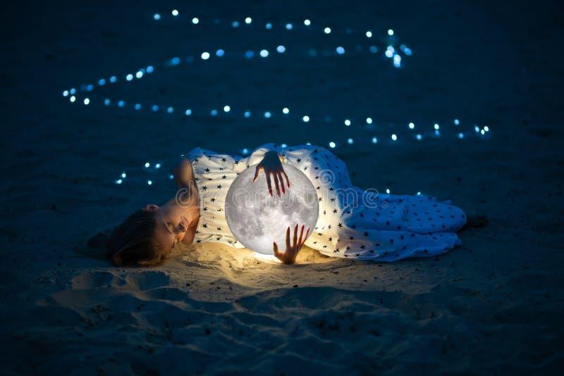 A menina atrativa bonita em uma praia da noite com areia e estrelas abraça a lua, fotografia artística fotos de stock