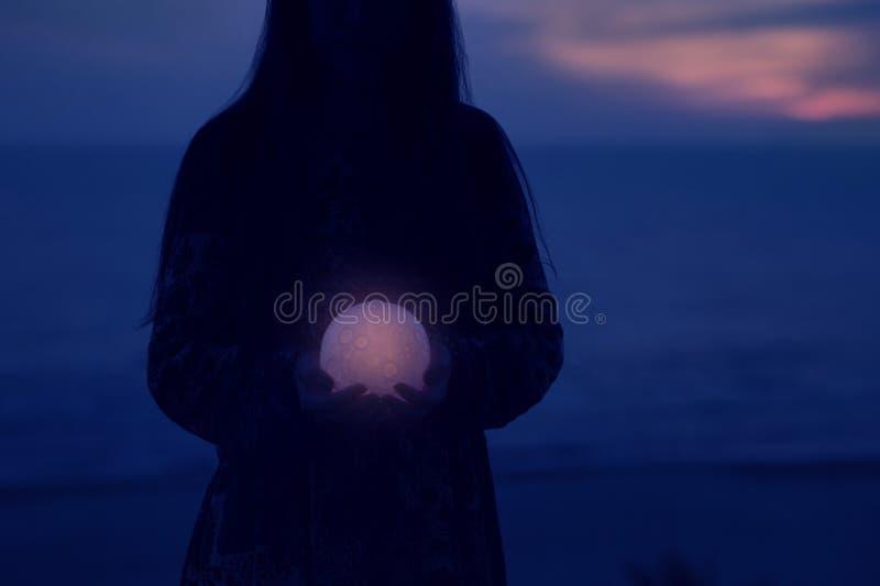 A menina atrativa bonita em uma praia da noite com areia e estrelas guarda a lua em suas m?os foto de stock