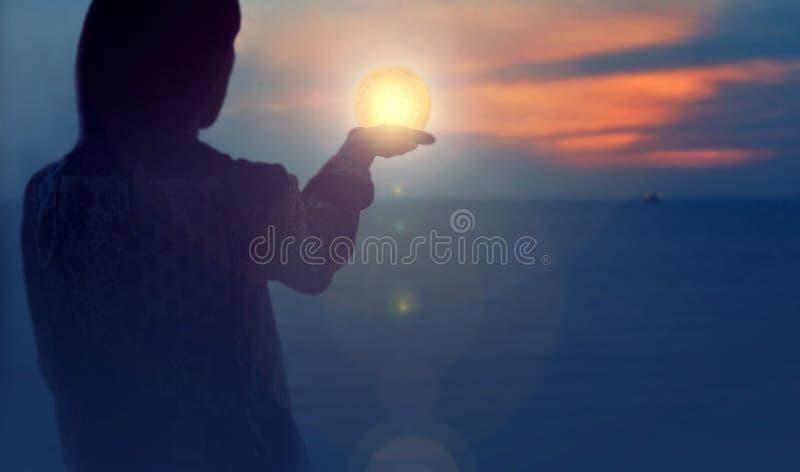 A menina atrativa bonita em uma praia da noite com areia e estrelas guarda a lua em suas m?os imagem de stock