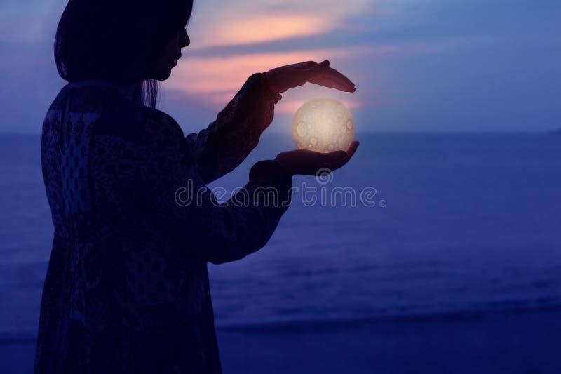A menina atrativa bonita em uma praia da noite com areia e estrelas guarda a lua em suas m?os imagem de stock royalty free
