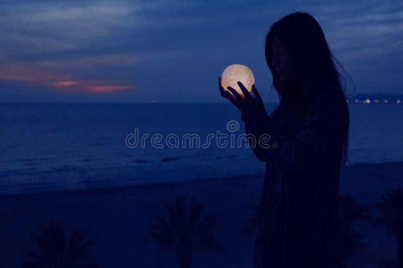 A menina atrativa bonita em uma praia da noite com areia e estrelas guarda a lua em suas m?os fotos de stock