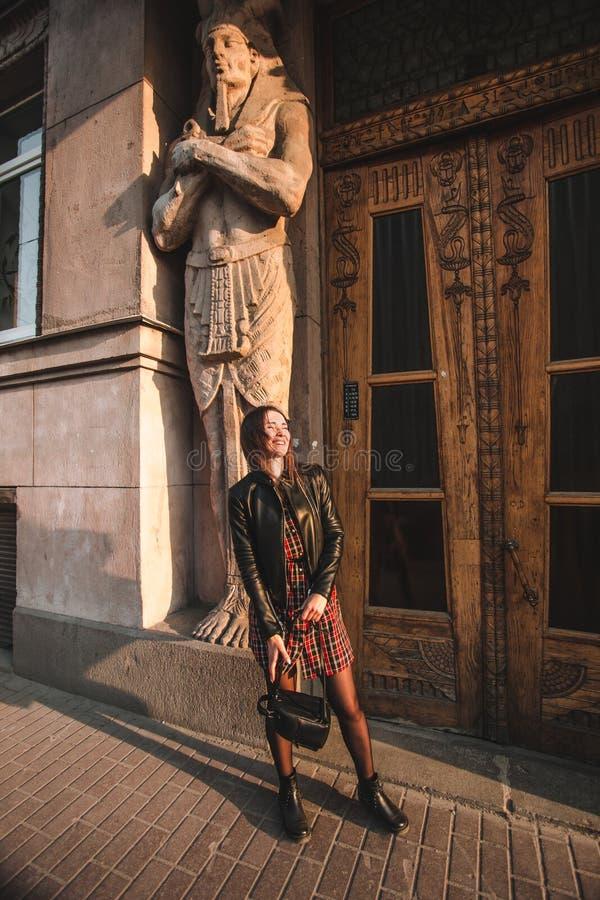 Menina atrativa com cabelo louro em um vestido em uma gaiola e em um casaco de cabedal preto iluminados pelo sol Atr?s do imagens de stock